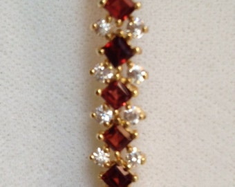 18 K yellow gold over sterling silver bracelet with garnets and clear stones