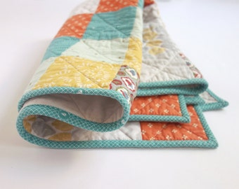 Patchwork baby quilt with teal, orange, gold, grey, white and minty green. Gender neutral, perfect for a boy or girl.