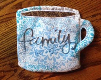 """Mug shaped mug rug, featuring appliqued fabric coffee and two tone stippling of """"family"""" in permanent marker."""