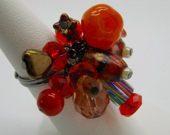 Bright orange beaded gunmetal ring is adjustable.  Many different unusual beads are included on this cute ring.