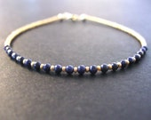 tiny lapis and gold seed beaded bracelet. thin string like bracelet. tiny lapis stackable bracelet minimalist jewelry