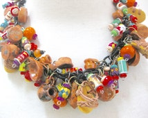 Mexican miniature clay pots, miniature moccasins, miniature food cans, bright colored Mexican beads on link necklace.