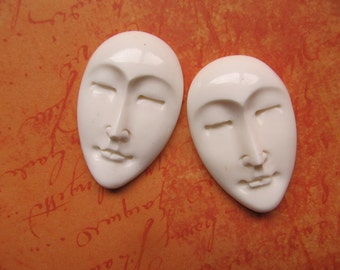 Two hand carved bone oval Moon, angel faces . 40 mm x 26 mm