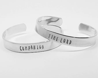 Time Lord and Companion: hand stamped SET of aluminum Doctor Who cuff bracelets