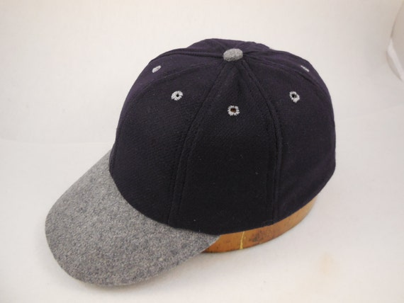 """Navy wool 8 panel cap with dark grey 2"""" visor, button and eyelets. Fitted with leather sweatband. Any size available"""