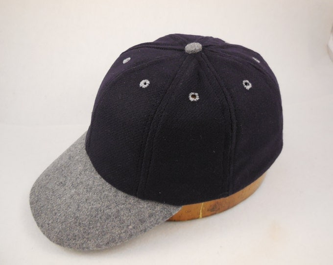"Navy wool 8 panel cap with dark grey 2"" visor, button and eyelets. Fitted with leather sweatband. Any size available"