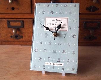 Pale blue mid century pattern cover book clock.  Albert Durer.