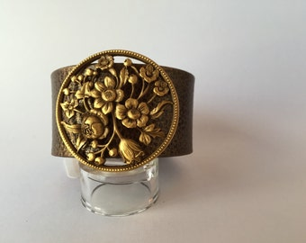 """Wide gold finished cuff featuring unique vintage goldtone ornate brooch. 1 1/2"""" wide and measures 7 3/4"""" from snap to snap."""