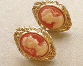 vintage gold tone metal earrings with peachy blush and cream cameo cabochon