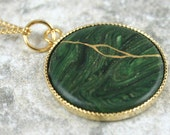 Kintsugi (kintsukuroi) style round pendant in swirled dark green polymer clay with gold repair set in a gold bezel on gold chain - OOAK