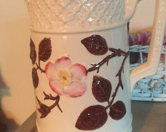 Antique pitcher with pink wild rose