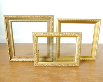 Three small gold wood picture frames with glass fronts