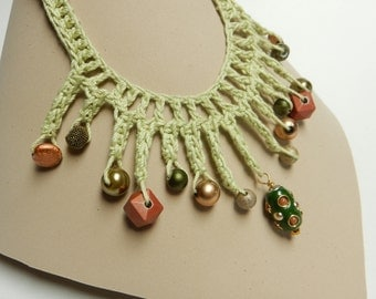Crocheted statement necklace in light green with whimsical beads in shades of copper and green