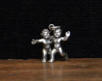 antique silver pendant of twin brothers or two naked boys