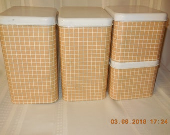 Vintage metal canister set of four, tan and white with lids.