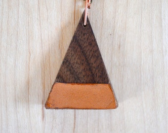 Hand carved walnut and leather pendent