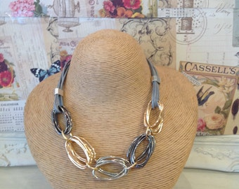 Grey leather necklace with silver , rose gold and gun metal grey coloured large oval links
