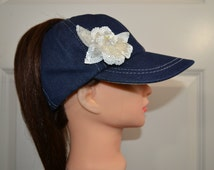 Baseball cap in navy denim with a sequined white flower has a high opening for a ponytail without the need for barrettes or holder