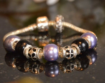 Charm bracelet with 7 purple and black beads