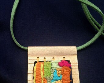 The necklace is finished in gold or silver with handcrafted embroidery in different colors.