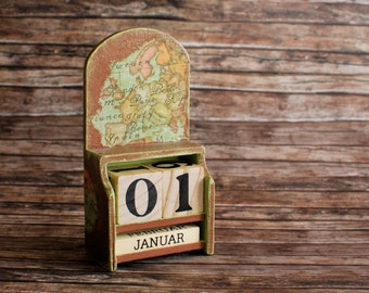 Perpetual wooden calendar with day cubes and months in a caddy box and map of OLD and NEW world
