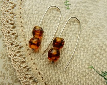 Sterling silver one of a kind earrings with honey brown vintage beads .