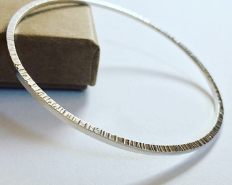 Silver bangle with textured sides