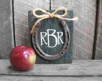 Custom monogram aged barn wood in the center of a real horse shoe.