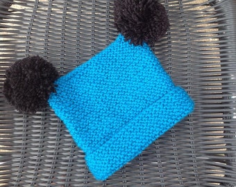 Hand knit baby hat with two sparkly pom poms.
