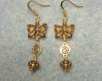 Brown Czech glass butterfly bead dangle earrings adorned with gold swirly connectors and brown Saturn beads.