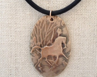 "Bronze horse trotting through the woods oval necklace. This oval pendant is 1 3/4 x 1  1/8""."