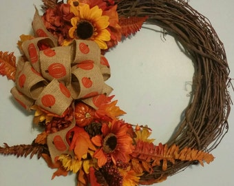 Fall grapevine floral wreath with pumpkin burlap bow.