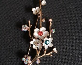 Metal and rhinestone flower brooch