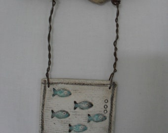 Fish impressed clay tile hung from driftwood