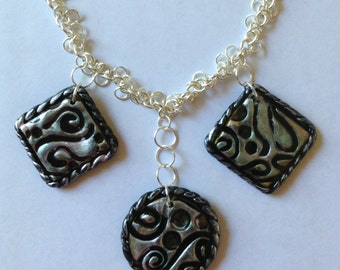 Three-medallion necklace on silver tone chain