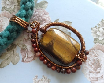 A kumihimo necklace with a stunning tigers eye pendant.
