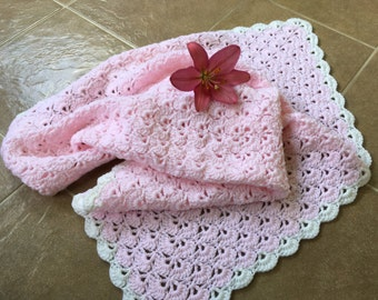 Pink crocheted baby blanket with white edges