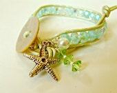 BOGO. Leather wrapped bracelet, soft ocean / beach colors. Blue, soft green, MOP button, starfish charm, bling. Single wrap.