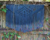 Large macramé wall hanging in color.