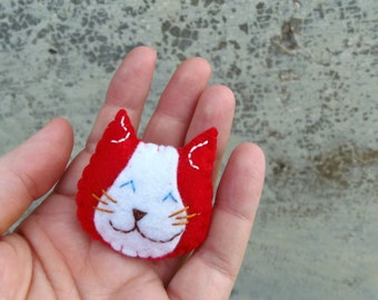 Cat brooch in red synthetic felt. Red felted cat pin gift for vegans. Stuffed and soft brooch portaying a smiling cat