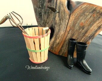 Handmade miniature wooden basket with tiny metal garden tools and a pair of miniature black rubber boots