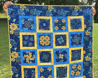 Scrappy blue and yellow quilt with blue flower yellow background