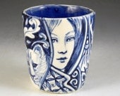 Blue and white porcelain story cup with cat, horned beast,  and faces