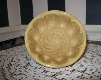 "Round five inch yellow ware mold in ""Turk's Head"" pattern"