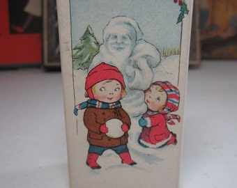 Adorable 1920's Dennison miniature bon bon box graphics of little boy and girl making a santa snowman, santa faces, stockings, toys, holly