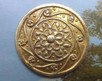 Metal button, antique.  Art Nouveau period, floral centre with a decorative border. c1890-1910.