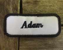 """Adam. A white work shirt patch that says """"Adam"""" in black script with black border"""