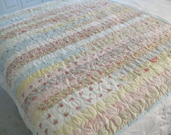 Handmade lap or crib quilt made of strips of beautiful fabric in soft colors.