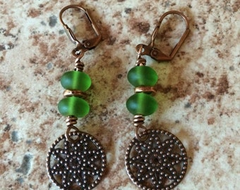 Gorgeous copper star earrings with green sea glass accents.
