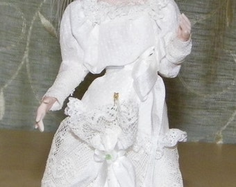 victorian lady dressed in lacy whie dress. large hat with green bow white flowers . Blond upsweep hair do.